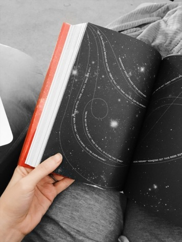 Photo of the page inside Illuminae in which the words flow across a star-filled page.